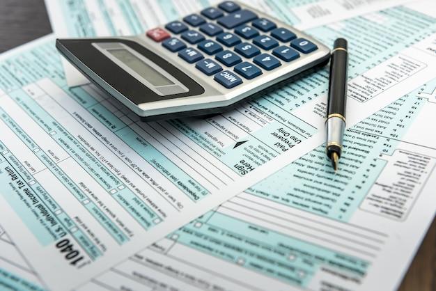 Pojęcie podatku 1040 formularz podatkowy z kalkulatorem na biurku. czas finansów