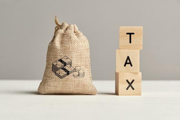 Pojęcie podatku obok worek pieniędzy. ścieśniać.