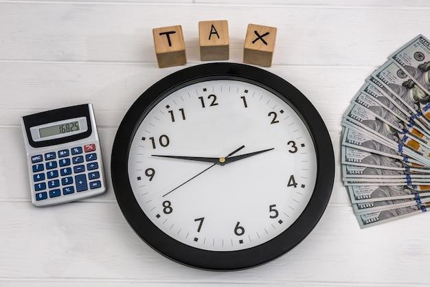 Pojęcie podatku z zegarem, banknotami dolara i kostkami