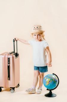 Pojęcie podróży, turystyki. dziewczyna na białym tle trzyma glob, w pobliżu stoi walizka