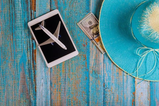 Pojęcie podróży turystyki przyrządów pastylki dotyka ochraniacza błękitny kapeluszowy przygotowanie dla podróżować dolarów amerykańskich banknoty