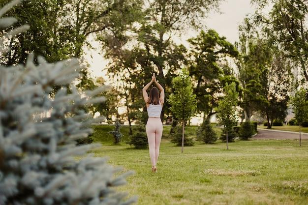 Pojęcie pokoju i zdrowia psychicznego, młoda kobieta w różowych legginsach stoi w pozie palmy w jodze.