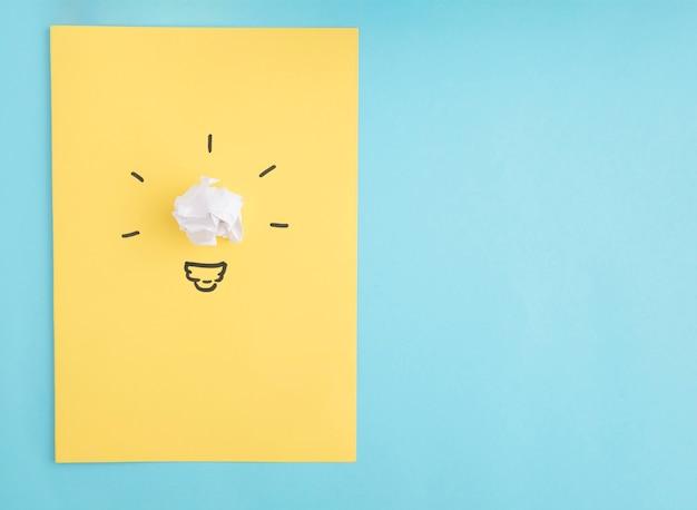 Pojęcie pomysł i innowacja z papierową piłką na żółtym papierze nad błękitnym tłem