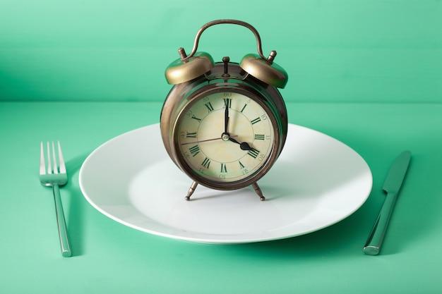 Pojęcie postu przerywanego, diety ketogenicznej, odchudzania. widelec i nóż skrzyżowane i budzik na talerzu