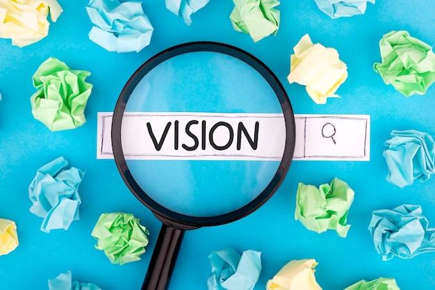 Pojęcie poszukiwania. tekst vision z lupą i kawałkami papieru na niebieskim tle.