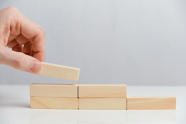 Pojęcie pracy zgodnie z planem. ręka trzyma drewniane klocki na białej przestrzeni.