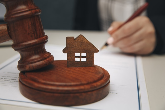 Pojęcie prawa nieruchomości. model domu i młotek.