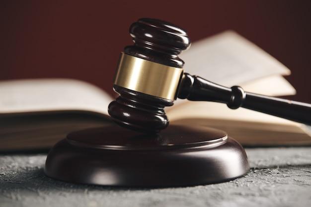 Pojęcie prawa - otwarta książka prawa z młotkiem drewnianym sędziów na stole w sali sądowej lub w biurze organów ścigania na czarnym tle.