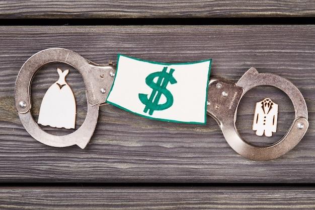 Pojęcie prawa przestępstw rodzinnych. kajdanki z miniaturowymi kostiumami i pieniędzmi na drewnie.