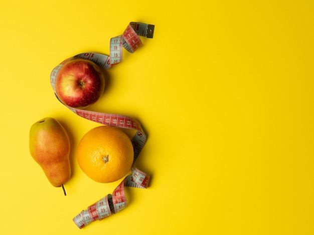 Pojęcie prawidłowego żywienia. soczyste owoce, jabłko gruszka pomarańcza owinięta miarką na jasnożółtym tle. widok z góry, kopia miejsca