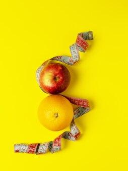 Pojęcie prawidłowego żywienia. soczyste owoce, jabłko i pomarańcza są owinięte miarką na jasnożółtym tle tworzącym ósemkę. widok z góry, kopia miejsca