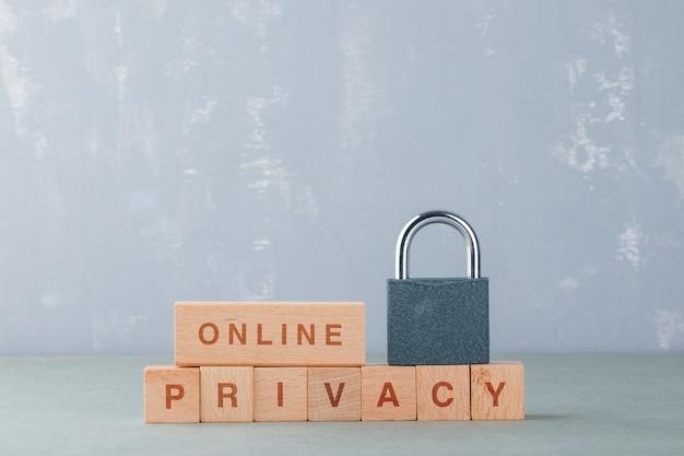Pojęcie prywatności danych z drewnianymi klockami ze słowami, zamek na nim widok z boku.
