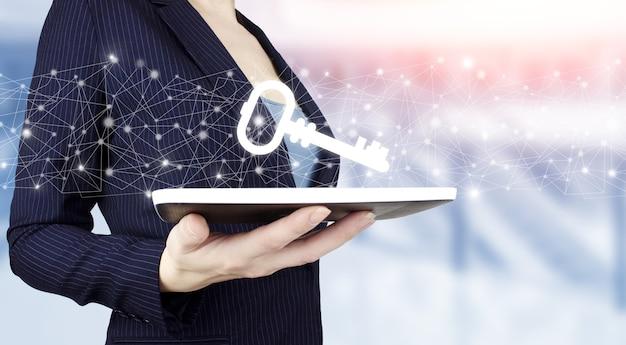 Pojęcie prywatności ochrony danych. rodo. ue. ręka trzymać biały tablet z cyfrowym hologramem kluczem na jasnym tle niewyraźne. sieć jest kluczem do sukcesu.