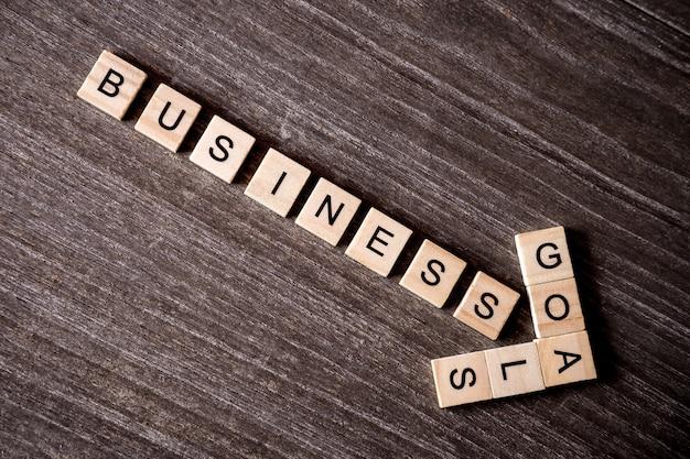 Pojęcie przedstawiający crossword z słowo biznesowym sukcesem cel z drewnianymi sześcianami