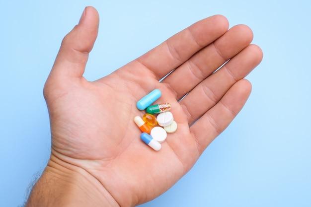 Pojęcie przyjmowania tabletek. ręka mężczyzny trzyma różne kapsułki pigułki