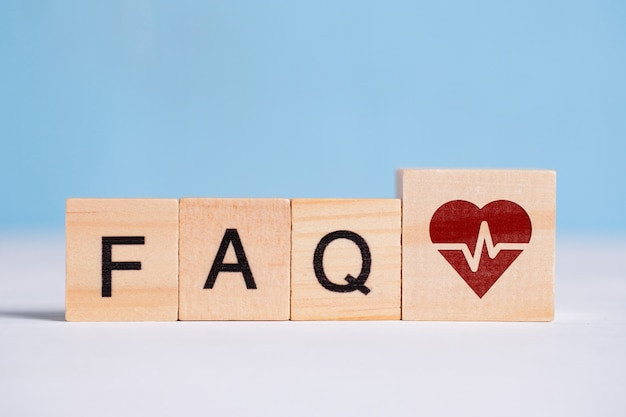 Pojęcie pytań i odpowiedzi na temat leczenia serca - faq. znak na drewnianym sześcianie obok liter.