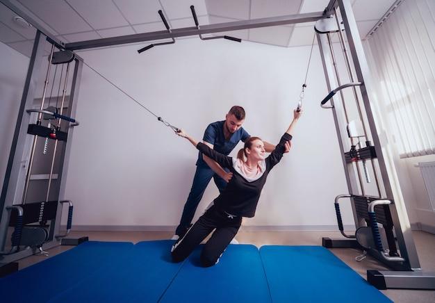 Pojęcie rehabilitacji. piękna młoda kobieta robi ćwiczenia na macie pod nadzorem fizjoterapeuty