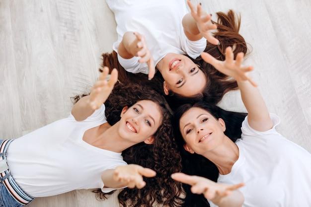 Pojęcie rodziny, pokolenia i kobiety - matka, córka leżące na podłodze i rozpostarte ramiona