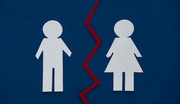 Pojęcie rozwodu. papierowe figurki mężczyzny i kobiety podzielone są na klasycznie niebieski.