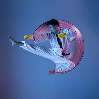 Pojęcie ruchu i działania w sporcie. pewny siebie koreański mężczyzna w kimonie ćwiczący walkę wręcz, sztuki walki. niebieskie tło, neonowe światło. sport, zdrowy styl życia, ruch. streszczenie projektu.