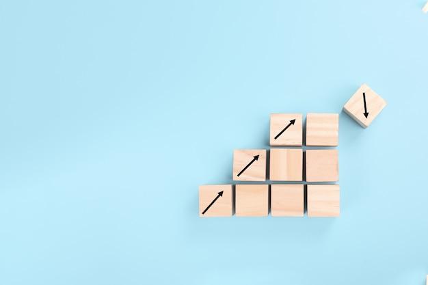 Pojęcie ryzyka w biznesie. wzrost na ułożonych drewnianych kostkach na niebieskim tle.