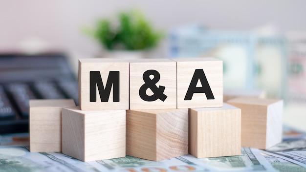 Pojęcie słowo m i a na drewnianych klockach na pięknej ścianie z zielonego kwiatu. słowo m and a na drewnianych kostkach z monetami i kalkulatorem na ścianie. pomysł na biznes