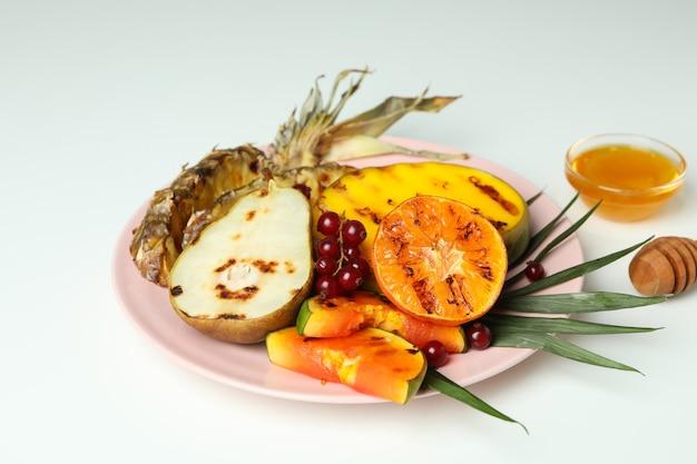 Pojęcie smaczne jedzenie z grillowanymi owocami na białym tle.
