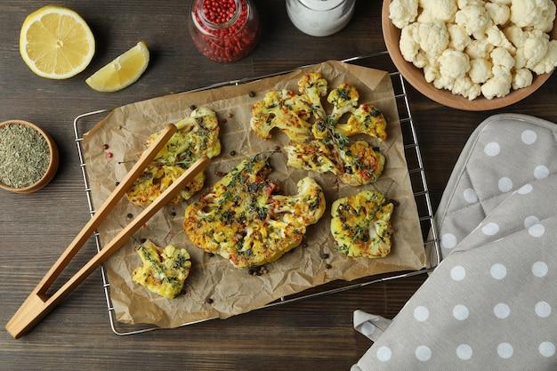 Pojęcie smaczne jedzenie z pieczonym kalafiorem na drewnianym tle.