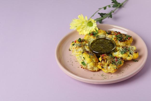 Pojęcie smaczne jedzenie z pieczonym kalafiorem na fioletowym tle.