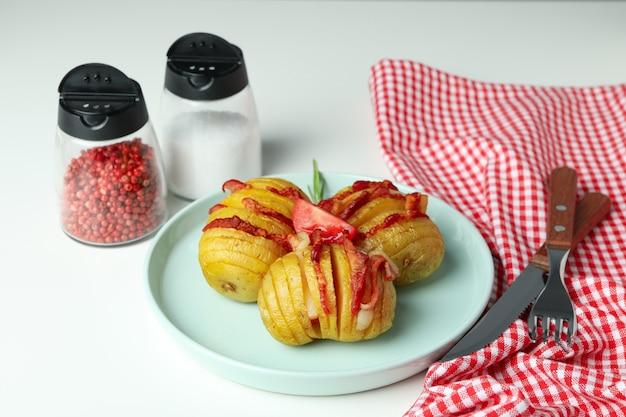 Pojęcie smaczne jedzenie z pieczonym ziemniakiem na białym tle.