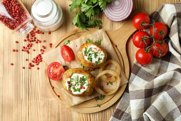 Pojęcie smaczne jedzenie z pieczonym ziemniakiem na drewnianym stole.