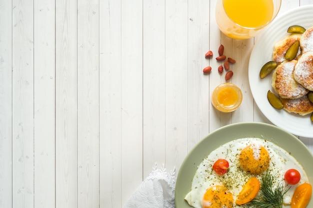 Pojęcie śniadania. jajka sadzone, placki twarogowe, śliwki i płatki owsiane z mlekiem, sok pomarańczowy na stole