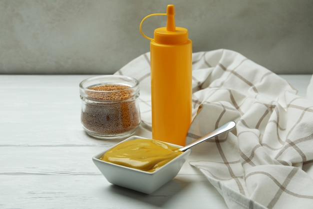 Pojęcie sosu z musztardą na białym drewnianym stole
