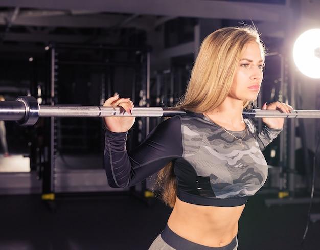 Pojęcie sportu, fitness, treningu i szczęścia - kobieta sportowy ze sztangą w siłowni.