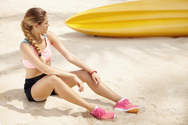 Pojęcie sportu i zdrowego stylu życia. piękna blondynka sportsmenka z warkoczem po przerwie, siedząc na piaszczystej plaży podczas ćwiczeń joggingu w słoneczny dzień. kaukaski kobieta biegacz relaks na świeżym powietrzu