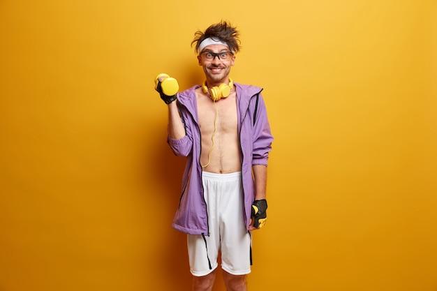 Pojęcie sportu, kulturystyki i zdrowego stylu życia. wesoły zmotywowany facet podnosi hantle dla silnych ramion, chce mieć męską siłę i muskularny tułów, ubrany w aktywny strój, odizolowany na żółtej ścianie