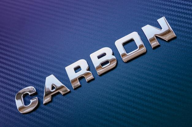 Pojęcie sportu, szybkości, wyścigów i lekkości. słowo carbon zapisywane ukośnie chromowanymi literami na fioletowo-niebieskim tle z włókna węglowego.