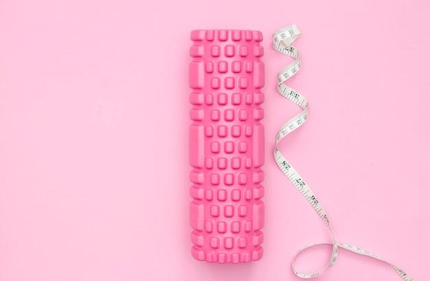 Pojęcie sprawności. różowy wałek fitness do treningu. taśma centymetrowa. utrata wagi. fitness kobiet w domu.
