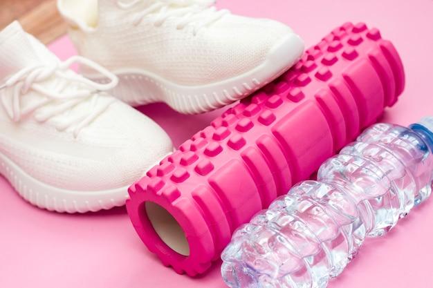 Pojęcie sprawności. różowy wałek fitness do treningu. trampki. fitness kobiet w domu.