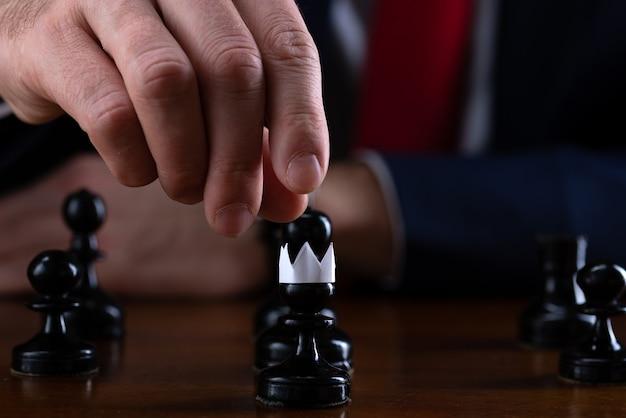 Pojęcie strategii i planowania biznesowego, biznesmen przy szachownicy przed wyłożonymi czarnymi pionkami, z których jeden jest w papierowej koronie, strategia i taktyka, gotowość do bitwy