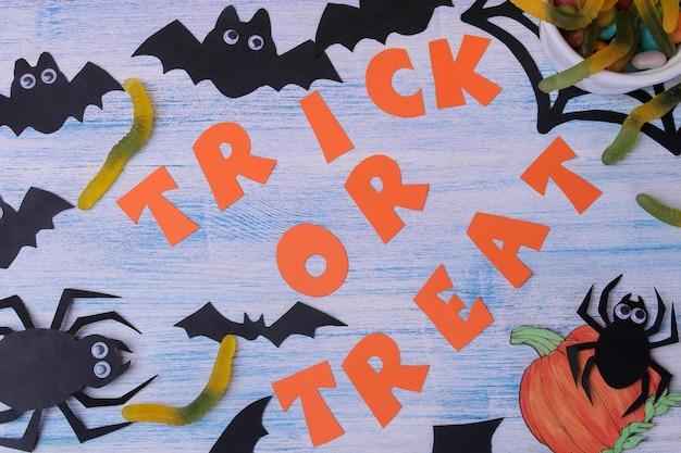 Pojęcie święta halloween. nietoperze i słodycze na niebieskim tle z napisem trick or treat widok z góry