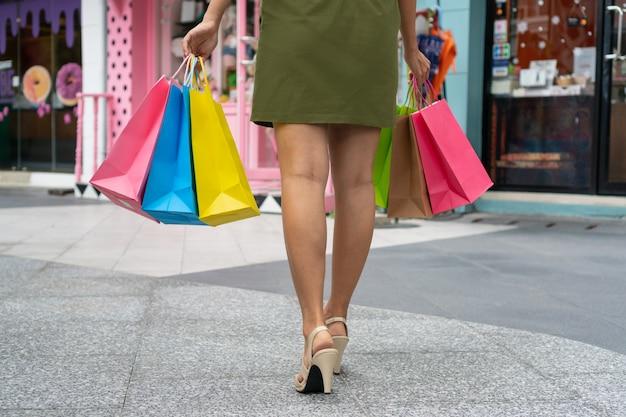 Pojęcie szczęśliwa kobieta robi zakupy torby i trzyma, zbliżenie wizerunki.