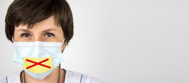 Pojęcie tajemnicy medycznej. lekarz z taśmą zaklejoną na ustach. zaklej usta i powstrzymaj się od prawdy o rzeczywistej liczbie przypadków rozprzestrzeniania się wirusa koronawirusa covid-19. tajemnica medyczna.