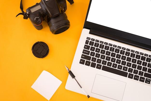 Pojęcie terminu fotografa. widok z góry stołu projektanta z laptopem pc, aparatem fotograficznym, białymi naklejkami i długopisem. skopiuj miejsce, żółte tło.