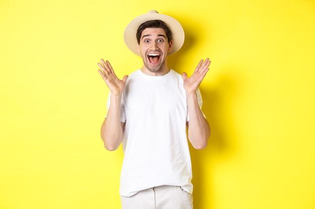 Pojęcie turystyki i lata. szczęśliwy młody człowiek w słomkowym kapeluszu patrząc zdziwiony, reagując na zdziwienie, stojąc na żółtym tle.