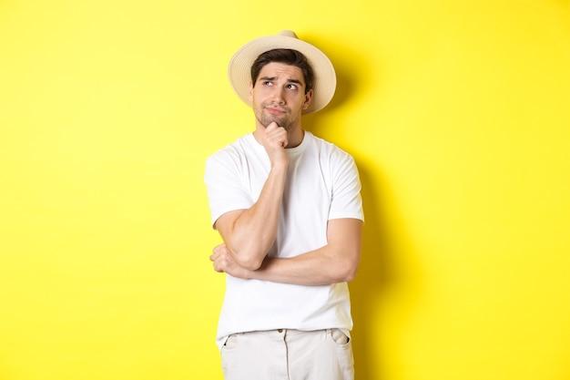 Pojęcie turystyki i lata. zamyślony turysta mężczyzna, patrząc w lewy górny róg i myślący, stojący w słomkowym kapeluszu i białej koszulce na żółtym tle.