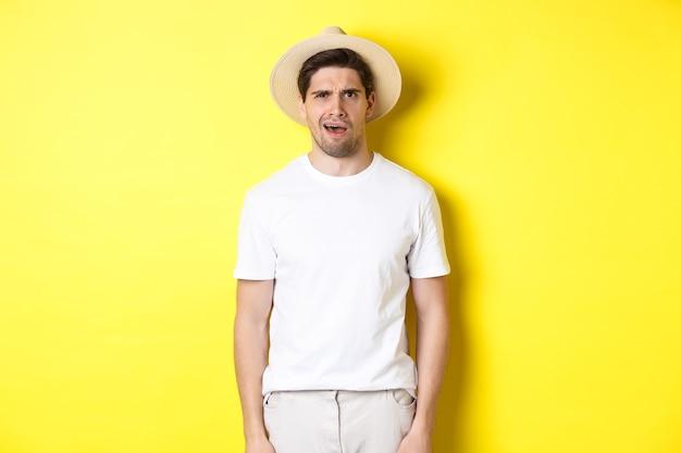Pojęcie turystyki i lata. zdezorientowany podróżnik w słomkowym kapeluszu, zdziwiony, nie może czegoś zrozumieć, stojący na żółtym tle.