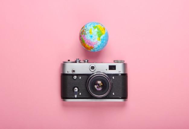 Pojęcie turystyki i podróży. glob, aparat na różowej pastelowej ścianie widok z góry. leżał na płasko