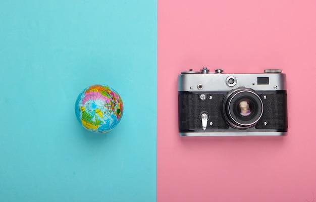 Pojęcie turystyki i podróży. globus, aparat na różowej niebieskiej pastelowej ścianie widok z góry. leżał na płasko