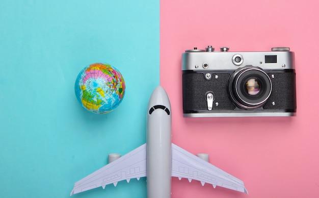 Pojęcie turystyki i podróży. globus, kamera i figurka samolotu pasażerskiego na różowej niebieskiej pastelowej ścianie widok z góry. leżał na płasko
